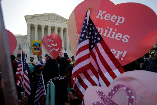 Immigration activists rally outside the Supreme Court as it hears arguments in a multistate challenge...