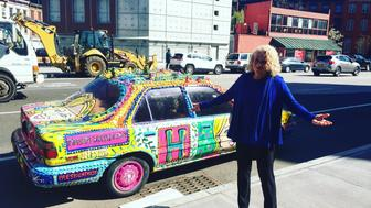 Carole King in front of a random car decorated in incredible Hillary Clinton paraphernalia.