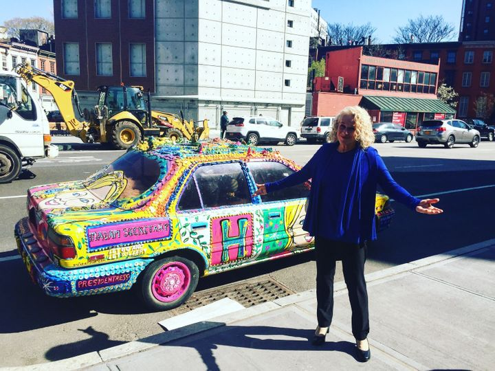 Carole King stands outside a random car parked in the West Village of New York City that is decked out in pro-Hillary Clinton