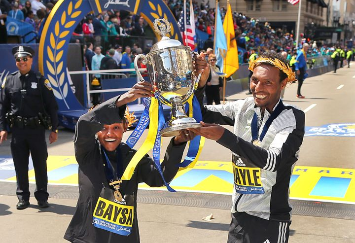 Men's winner Lemi Berhanu Hayle of Ethiopia and women's winner Atsede Baysa of Ethiopia hold up a trophy at the finish line o