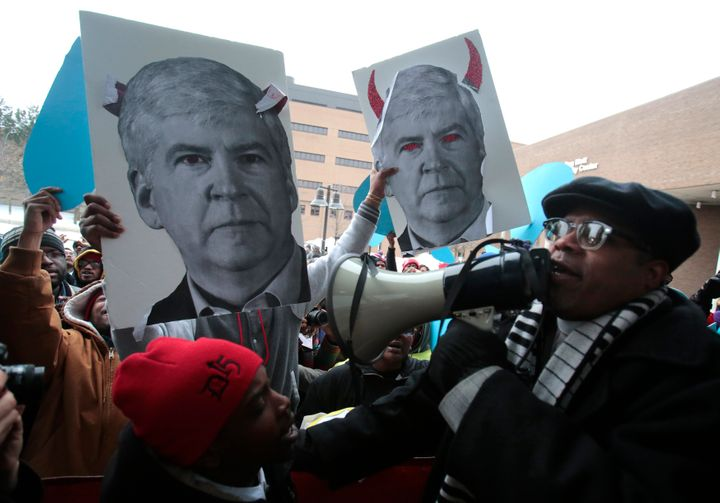 Demonstrators hold images of Michigan Gov. Rick Snyder outside the Democratic presidential debate in Flint, Michigan on&