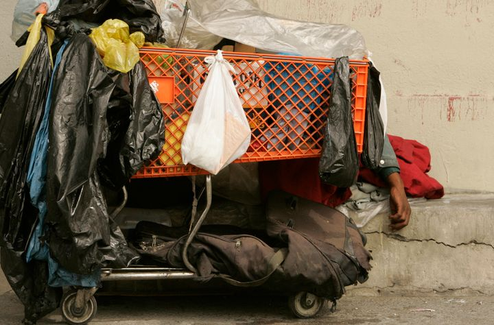 A homeless man sleeps behind his shopping cart on a sidewalk on downtown Los Angeles.
