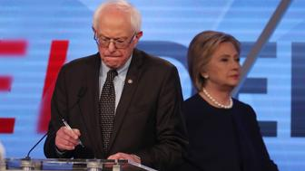 Democratic U.S. presidential candidate Senator Bernie Sanders writes on his notes as his rival Hillary Clinton walks behind him to her podium during a commercial break at the Univision News and Washington Post Democratic U.S. presidential candidates debate in Kendall, Florida March 9, 2016.   REUTERS/Carlo Allegri