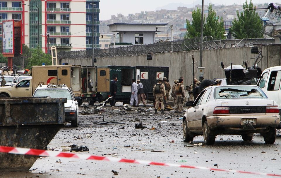 Policemen and officials inspect the site of an attack in front of a government office in Kabul, Afghanistan, on Apr