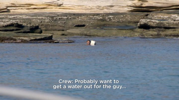A man, said to have been castaway on an island for more than two days, is seen swimming out to a passing camera crew.