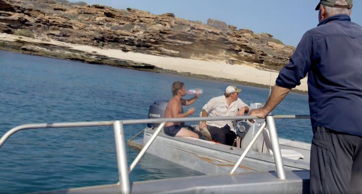 The castaway is seen drinking a bottle of water after being taken onboard the film crew's boat.