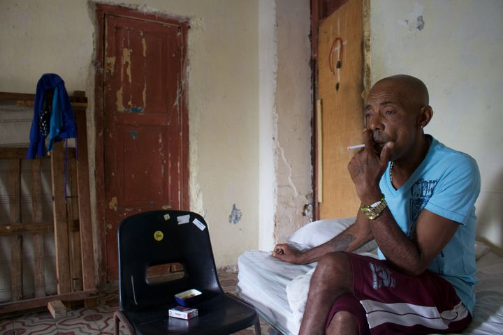 Francisco Jesús Jiménez, 58, smokes a cigarette in his apartment in the working-class neighborhood of Cayo Hues