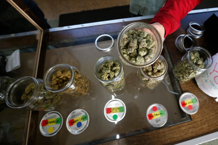 A volunteer displays jars of dried cannabis buds at the La Brea Collective medical marijuana dispensary in Los Angeles, Calif