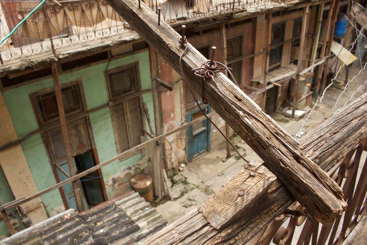 A splintering four-by-four supportsthe second-floor balcony in Francisco Jesús Jiménez's dilapidated apar