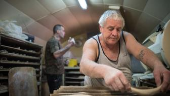 Michel Flamant (R) and Jerome (L) work in their bakery on March 23, 2016, in Dole, eastern France. Michel Flamant, the owner of the bakery decided to teach baking and pastry to Jerome and to sell him his bakery for one symbolic euro, after Jerome saved his life.  / AFP / SEBASTIEN BOZON        (Photo credit should read SEBASTIEN BOZON/AFP/Getty Images)