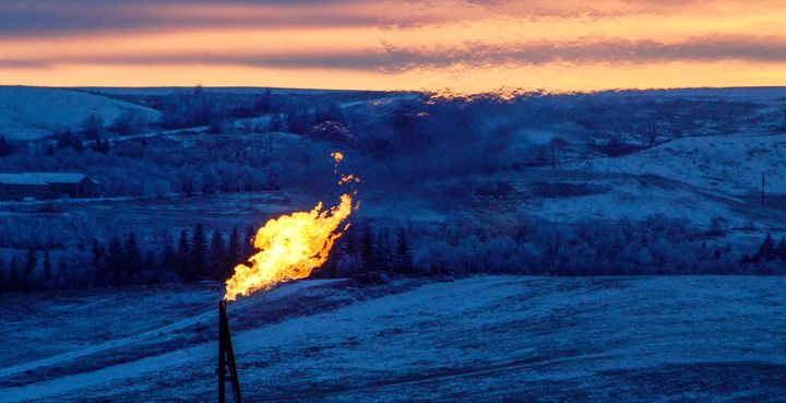 A natural gas flare on an oil well pad burns as the sun sets outside Watford City, North Dakota.
