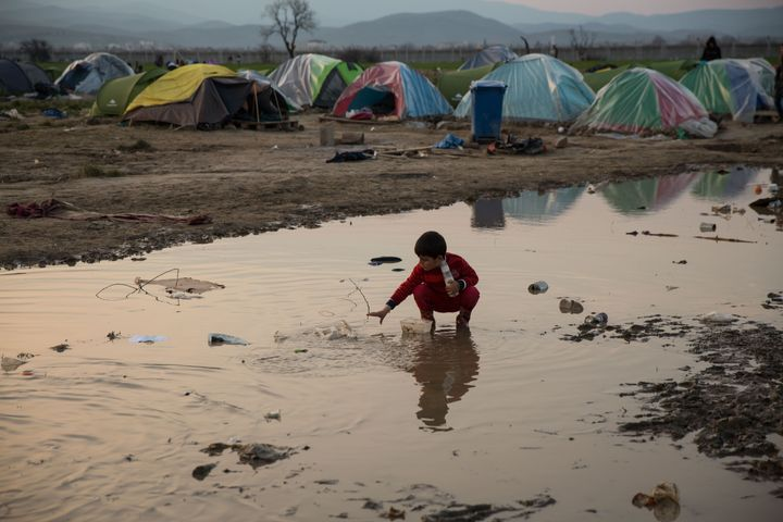 IDOMENI, GREECE - MARCH 19: Children play in puddles of rain water at the Idomeni refugee camp on the Greek Macedonia border
