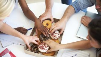 Coworkers reaching for a tasty snack during a brainstorming session