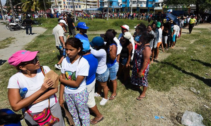 Local residents line up to receive food aid in Manta, Ecuador, after the powerful 7.8-magnitude quake struck Ecuador's Pacifi