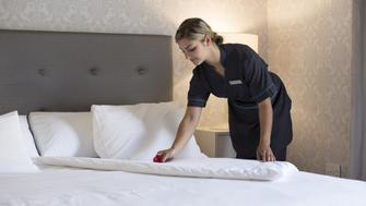 Chambermaid laying a flower onto the sheets while making a bed in a hotel room