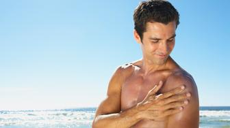 Man applying sun block or suntan lotion outdoors
