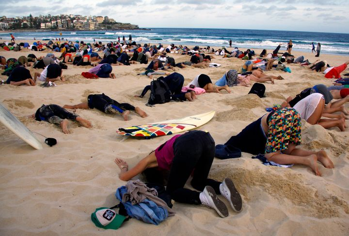 Australians stick their heads in the sand in protest of the government's climate policies in 2014.