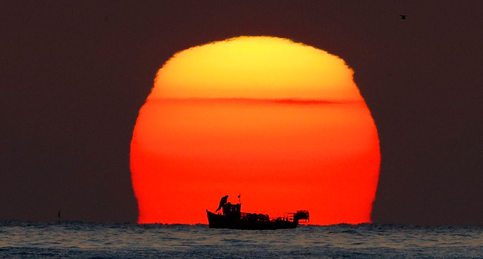 A lobster fisherman checks his pots as the sun rises over his small fishing boat in the North Sea near...