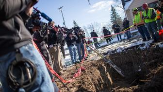 Camera crews look on as workers replace an old lead pipe with a new safer copper pipe at a home in Flint, Michigan, March  4, 2016.  The city exposed 100,000 residents to lead poisoning after cutting water treatment costs.  / AFP / Geoff Robins        (Photo credit should read GEOFF ROBINS/AFP/Getty Images)