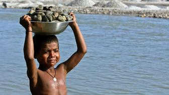 Munna Reja, an eight-year-old child labourer, carries stones on the banks of the Balason river, on the outskirts of the northeastern Indian city of Siliguri October 10, 2006. A ban on child labour in households, street food stalls and hotels came into effect in India on Tuesday, but activists doubt how authorities will implement the new rules, given their track record on implementing similar bans.    REUTERS/Rupak De Chowdhuri    (INDIA)