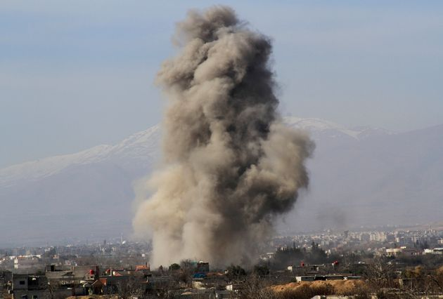 Smoke rises after what activists say werebarrel bombs dropped by government forces in Daraya explode.Some...