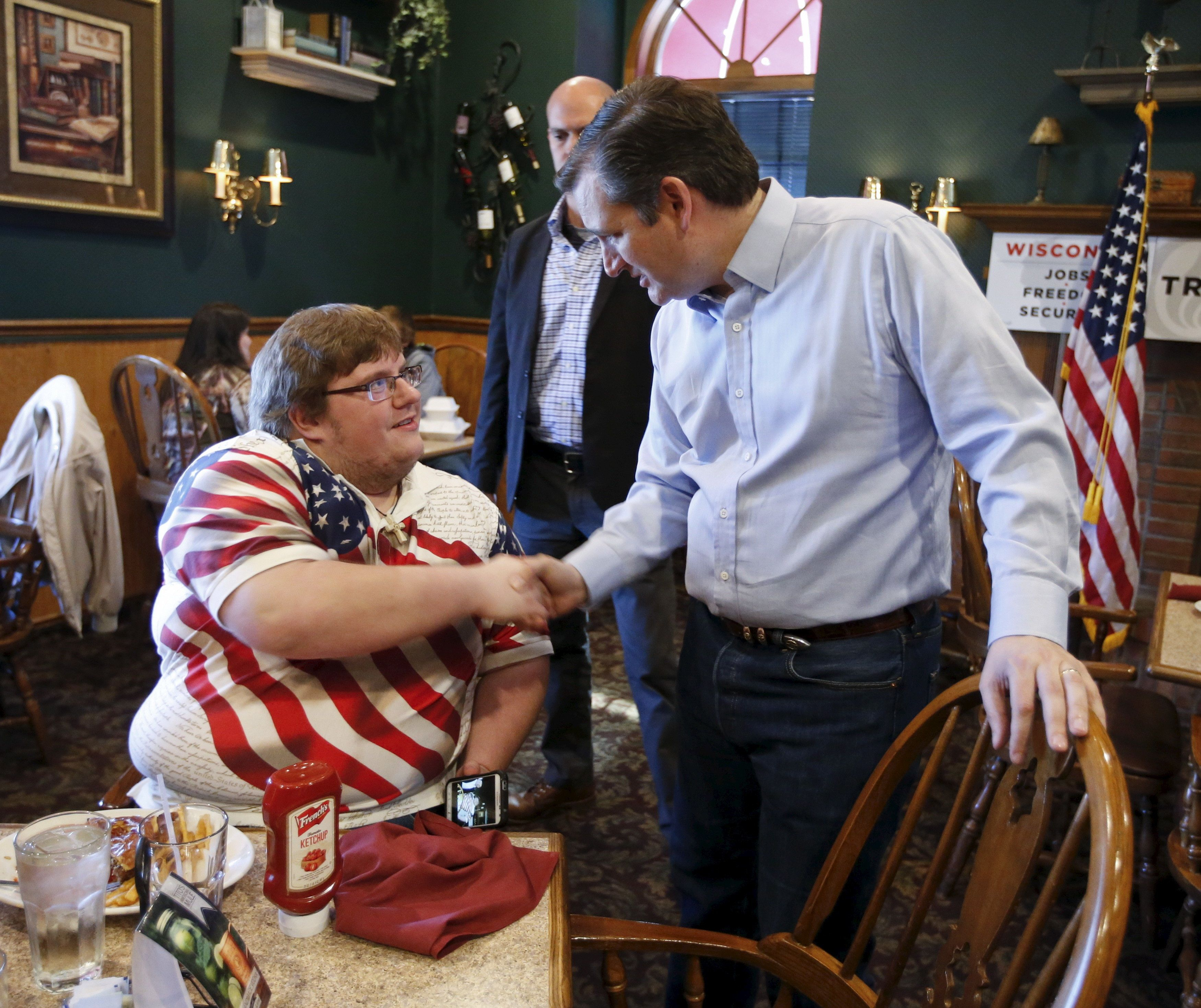 U.S. Republican presidential candidate Ted Cruz shakes hands with a 2510 Restaurant guest during a campaign stop in Wausau April 3, 2016. REUTERS/Kamil Krzaczynski