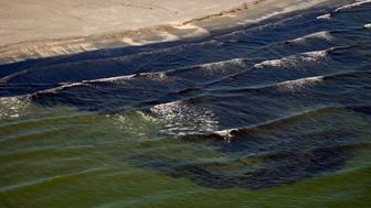 Oil from the Deepwater Horizon spill is visible in the surf off Fourchon Beach, Louisiana July 9, 2010. REUTERS/Lee Celano (UNITED STATES - Tags: DISASTER ENVIRONMENT ENERGY BUSINESS)