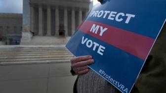 UNITED STATES - FEB 27 : Protesters hold signs outside the Supreme Court  as the Shelby County, Alabama v. Holder oral arguments where set to begin at the Supreme Court on the importance of protecting the right to vote for all Americans on February 27, 2013.  (Photo By Douglas Graham/CQ Roll Call)