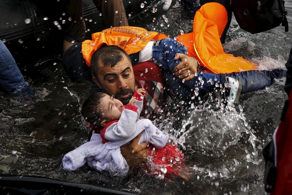 A Syrian refugee holds onto his children as he struggles to walk off a dinghy after crossing from Turkey to the Greek island