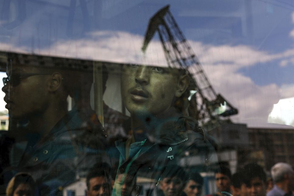 An Afghan migrant looks out a bus window after reaching the port of Piraeus in Greece. He and 2,500 other migrants arriv