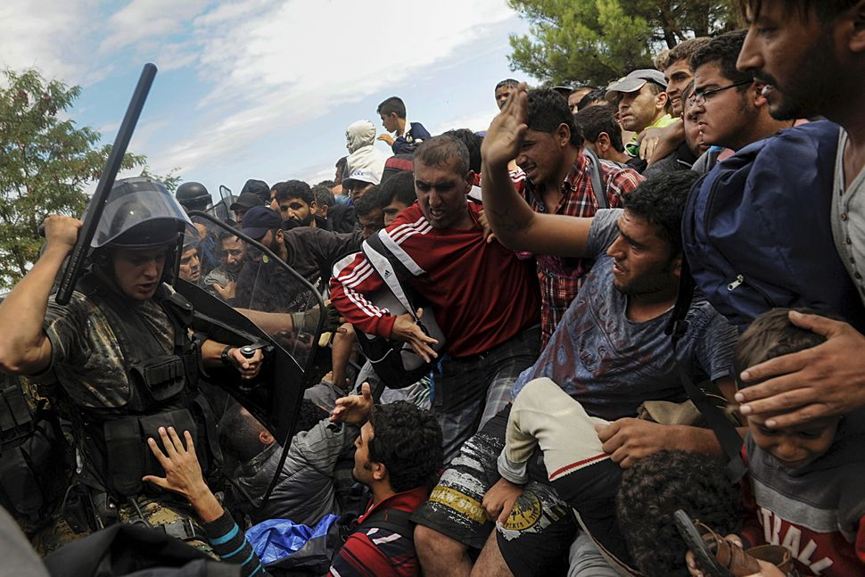 A Macedonian police officer inthe Greek border town of Idomeniraises his baton to stop migrants from entering Mac