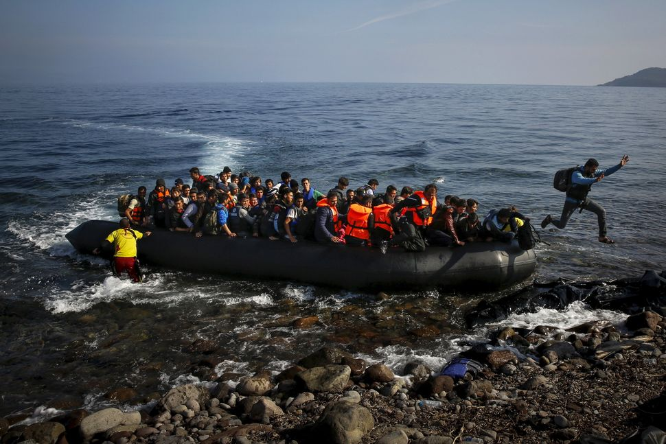 An Afghan migrant jumps off an overcrowded raft onto the Greek island of Lesbos on Oct. 19, 2015.