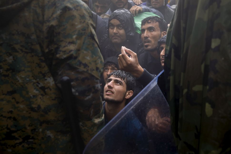 Migrants and refugees near Idomeni, Greece, beg Macedonian police to allow them across the border during a rainstorm on Sept.