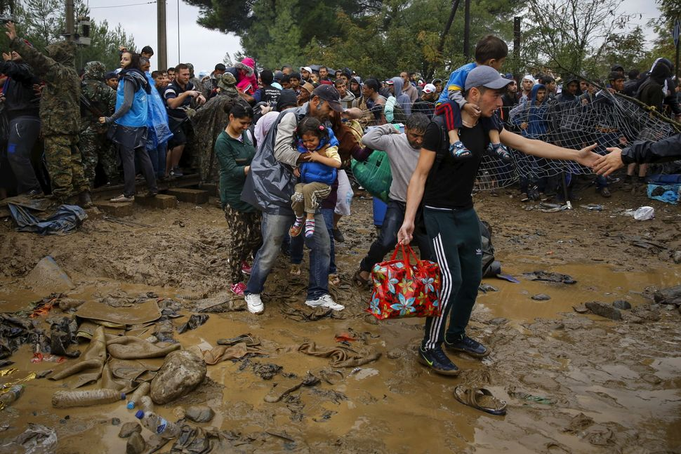 Syrian refugees walk through the mud as they cross the border from Greece into Macedonia on Sept. 10, 2015.