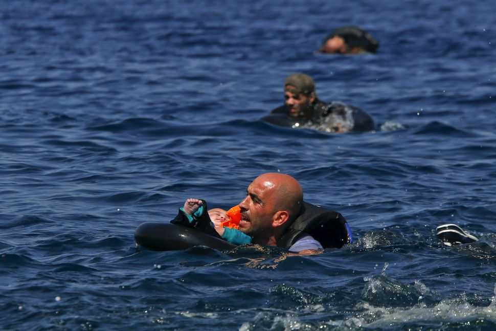 A Syrian refugee holding a baby swims toward shore after their dinghy deflated off the coast of Lesbos, Greece, on