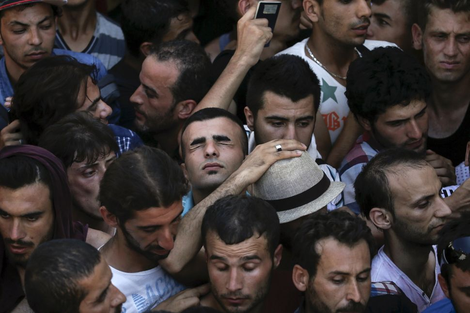 A Syrian refugee tries to catch his breath as he stands in a crowded line to register at a stadium on the Greek island o