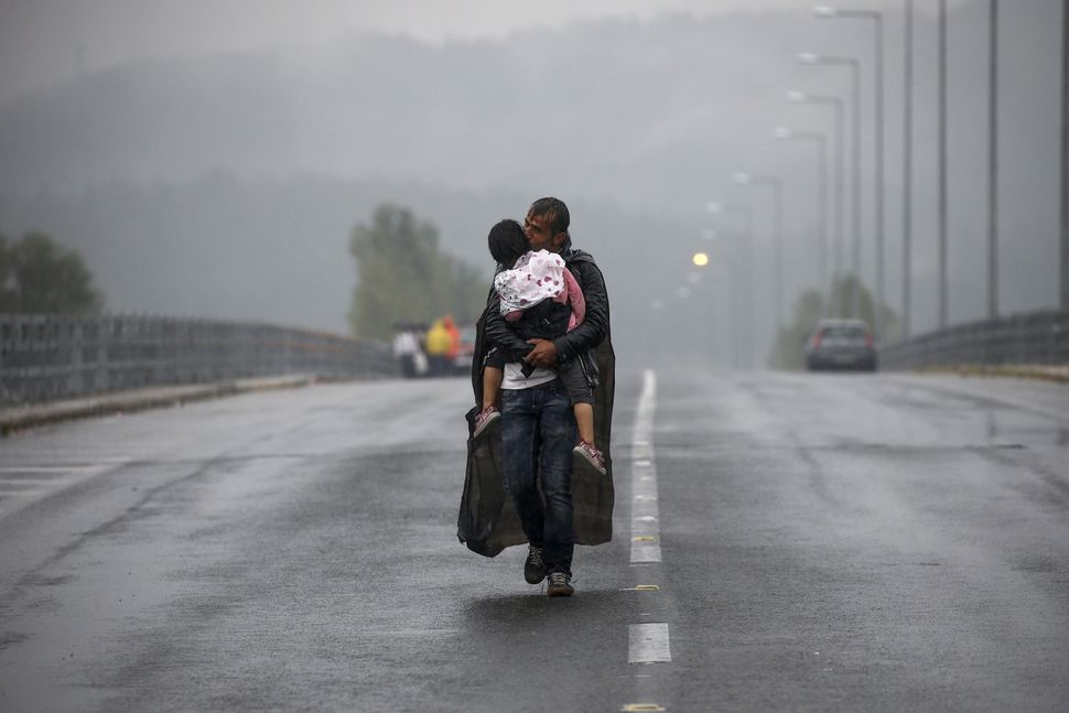 A Syrian refugee kisses his daughter as he walks through a rainstorm towards Greece's border with Macedonia on Sept. 10, 2015