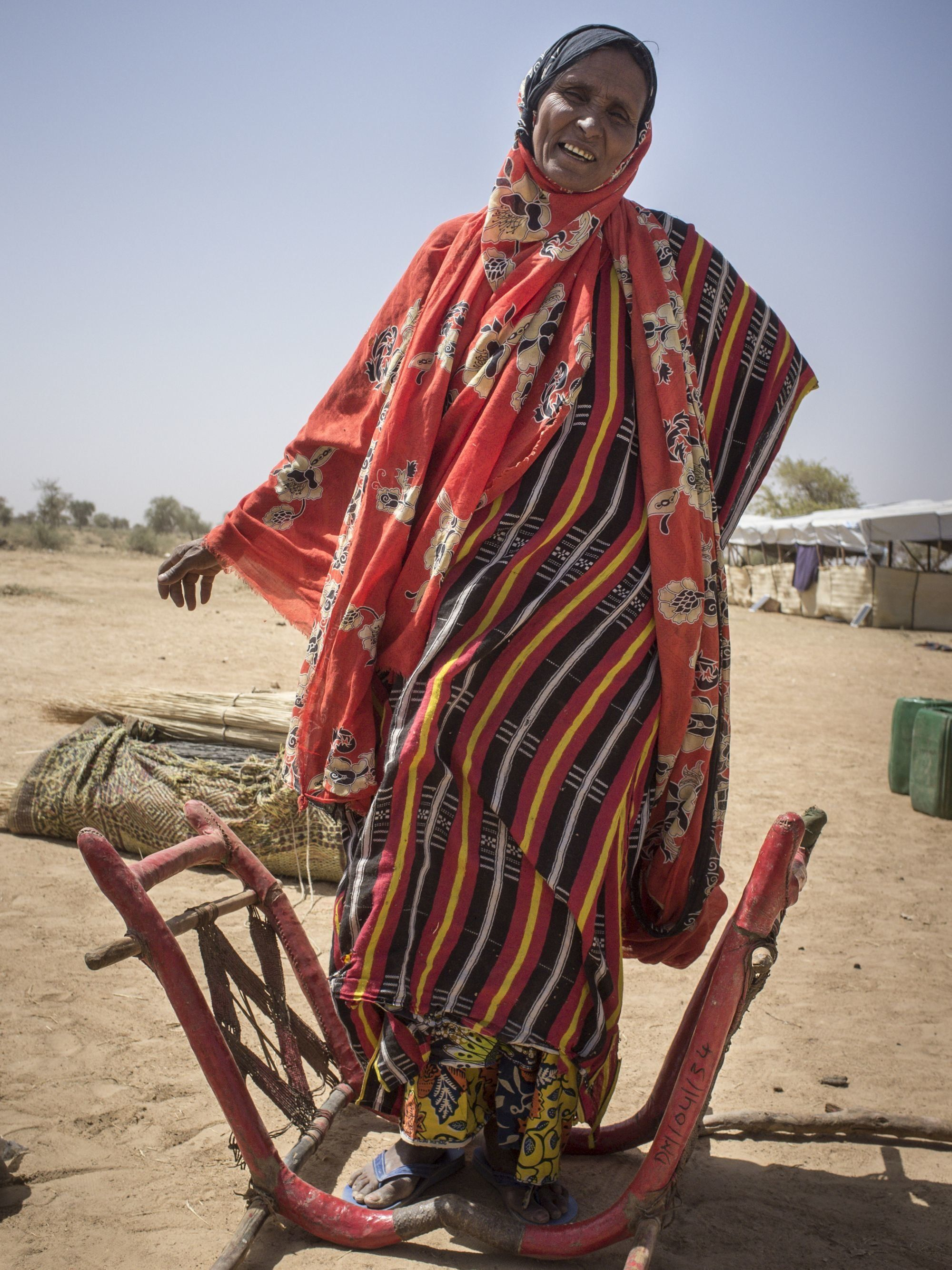 A Tuareg woman from Timbuktu stands next to the livestock chair she rode upon to reach Burkina Faso. She fled Mali by camel in 2013.