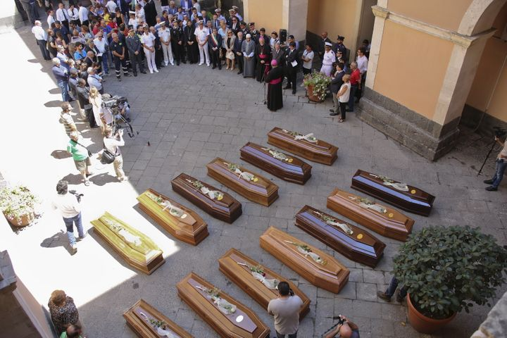 Coffins of 13 unidentified migrants who died in the April 19, 2015, shipwreck are seen during a funeral service in Catania, I