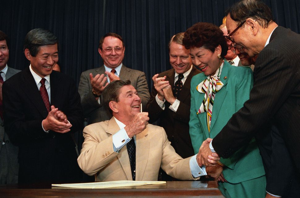 President Ronald Reagan signs the Civil Liberties Act of 1988, acknowledging that the United States really didn't need to inc