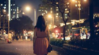 Desperate and lonely  woman walking along the city street at night time.