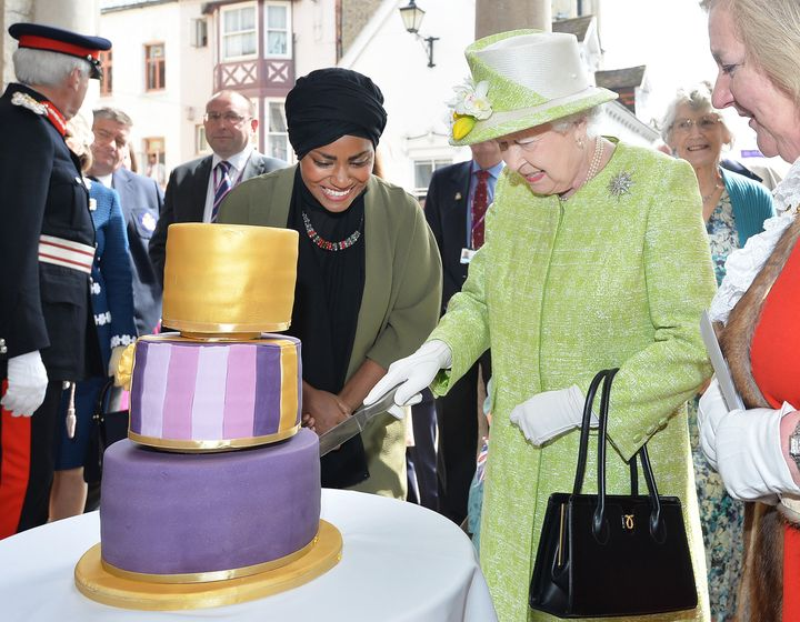 The Queen cuts a cake baked for her by Nadiya Hussain, the winner of the Great British Bake Off, a popular baking competition