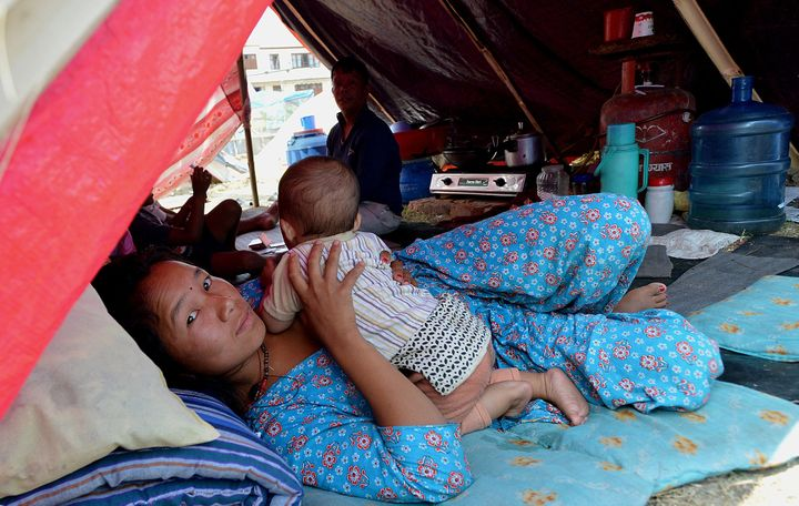 Nepalese residents lie in a temporary shelter at a relief camp for earthquake survivors in Kathmandu on May 21, 2015, after m