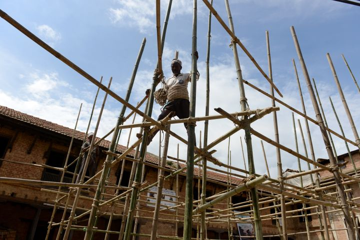 A Nepalese labourer works on bamboo scaffolding during repairs to a temple damaged in an earthquake at the village of Khokana