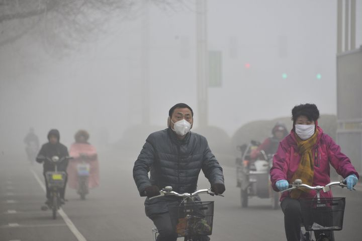People ride their bikes in heavy smog on Feb.12, 2015 in Liaocheng, China.