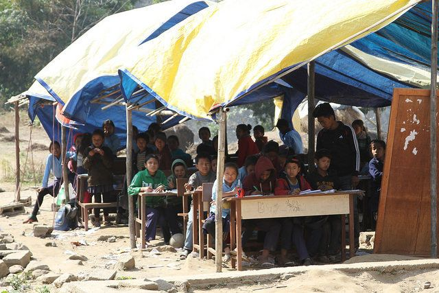 Children sit at their desks ina temporary learning center in Sindhupalchok. Volunteers have constructed makeshift class