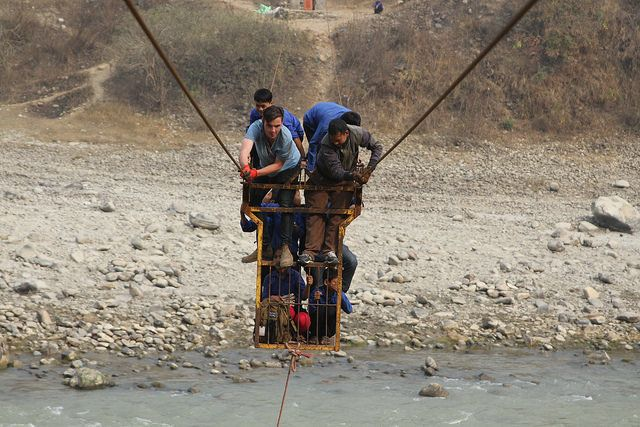 Schoolchildren cross a river in Dhading district with Christian Stephens, one of the producers of Theirworld's film. Many chi