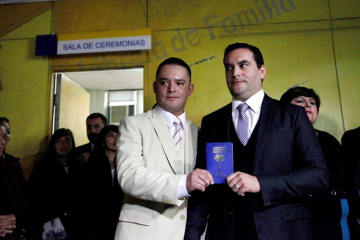 The couplepose with their civil union identification booklet.