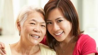 Portrait Of Chinese Mother With Adult Daughter Relaxing At Home Smiling To Camera