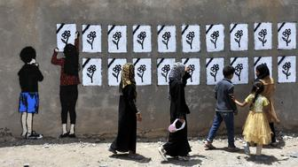 SANAA, YEMEN - MAY 18: Yemeni people look at graffiti sprayed on a wall commemorating the victims who were killed in Saudi-led coalition airstrikes in Sanaa, Yemen on May 18, 2015. (Photo by Mohammed Hamoud/Anadolu Agency/Getty Images)